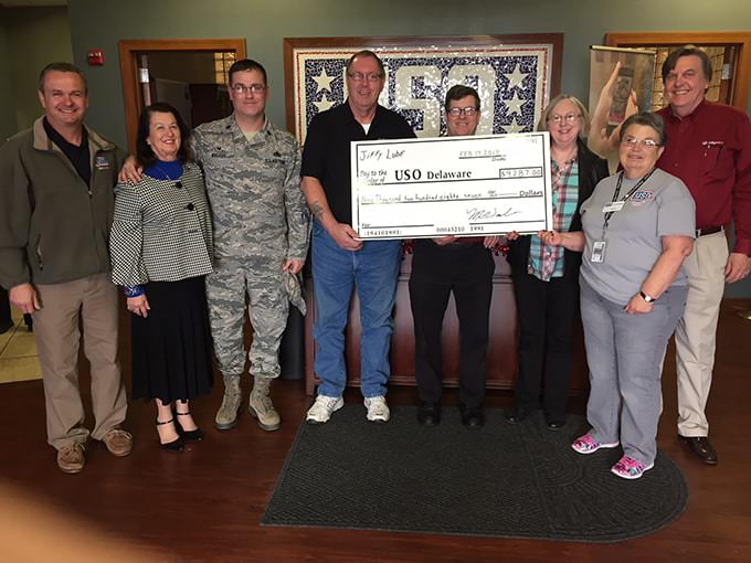 Employees holding large USO Check